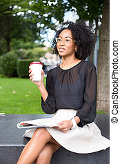 coffee break - young woman outdoors enjoying a coffee and...