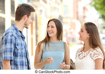 Three friends talking taking a conversation on the street -...