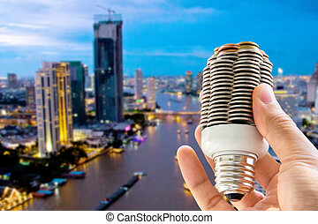 eco energy concept - hand holding light bulb and cityscape...