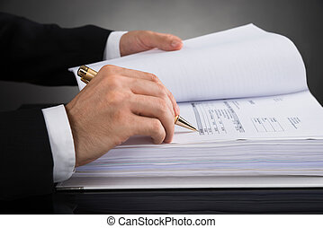 Businessperson Calculating Invoice - Close-up Of...