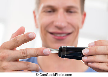 Man Checking Blood Sugar Level - Close-up Of Young Happy Man...