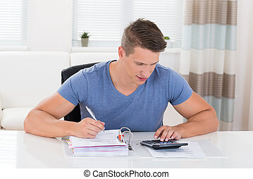 Young Man Calculating Invoice With Calculator At Desk