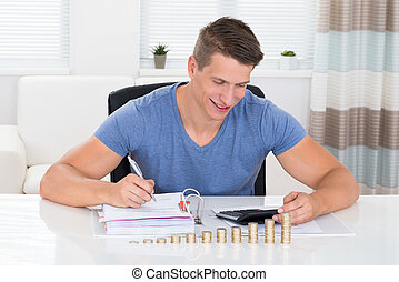 Man Calculating Invoice With Coins At Desk - Happy Man...