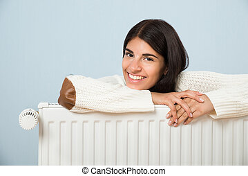 Woman Leaning On Radiator - Young Happy Woman Leaning On...