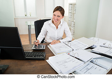Businesswoman Calculating Financial Data At Desk - Happy...