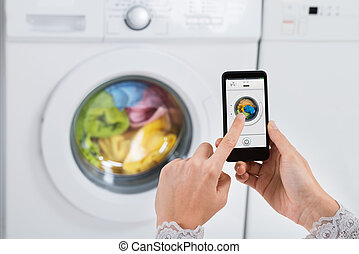 Person Hands Operating Washing Machine With Mobile Phone
