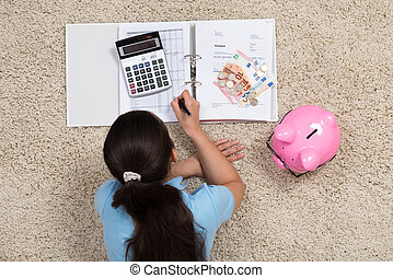 Woman Doing Calculation At Home - Young Woman Lying On...