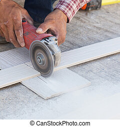 carpenter hands using electric saw on wood at construction...