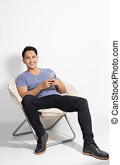 man holding a handphone while sitting on the chair - A...