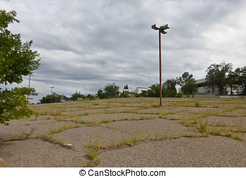 Abandoned parking lot with grass growing through cracks