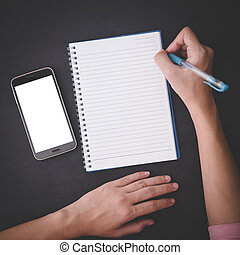 Hand holding a pen, with a notes and handphone, black...