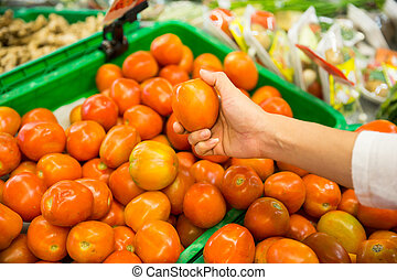 Woman's hand picking a tomato on a market