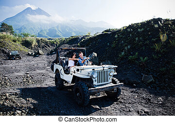 Mixed race couple riding a jeep off road