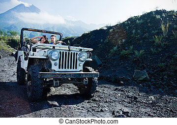 Mixed race couple riding a jeep off road - A portrait of...
