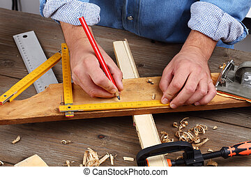 carpenter hand with yardstick and pencil
