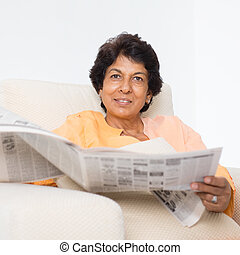 Indian mature woman reading newspaper - Portrait of a 50s...