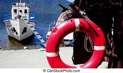 dock the boat lifebuoy - the boat is at the shore of a large...