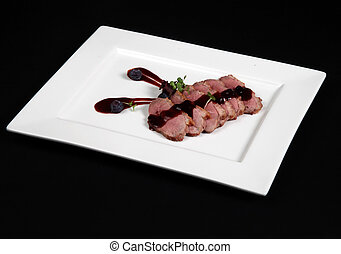 duck meat with cranberry cream in white plate on a black...