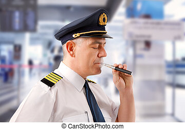Airline pilot with e-cigarette - Airline pilot wearing...