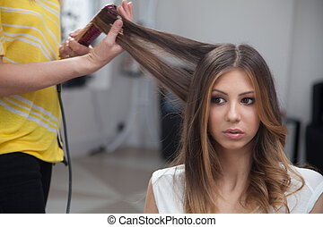 Beauty salon - Hairstylist curling hair woman client in...