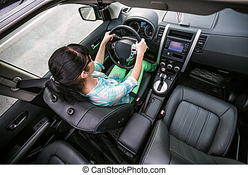 Woman behind the wheel of a car.