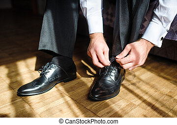 Business man tying shoe laces on the floor. Close-up.
