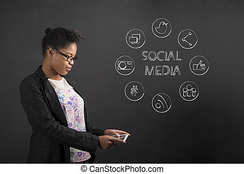 African American woman with tablet social networking on blackboard background