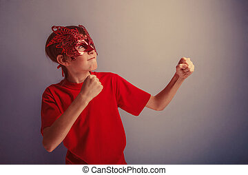 Boy teenager twelve years in red shirt in the mask, super...