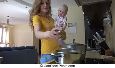 woman hold baby kitchen - Young woman in yellow holding baby...