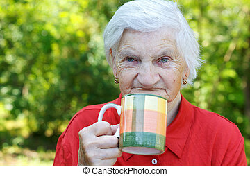 Healt care - Elderly woman drinking a cup of tea outdoor on...