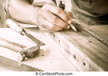 Close Up view of a carpenter using a straightedge to draw a...