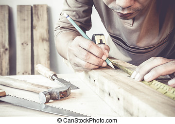 Serious young male carpenter working with wood in his workshop.