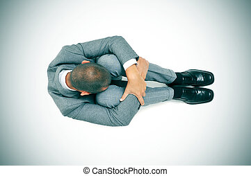 businessman curled up in the floor with his head between his...