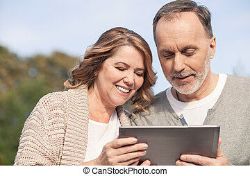 Cheerful old married couple is watching a tablet - Pretty...