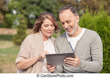 Pretty old husband and wife are using a tablet - Cute mature...