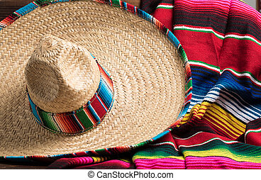 Mexican Sobrero and Serape blanket on yellow background with...