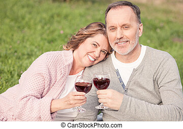 Cute old married couple is enjoying drink in park - Pretty...