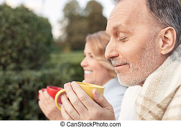 Cheerful old loving couple is drinking tea outdoors - Cute...