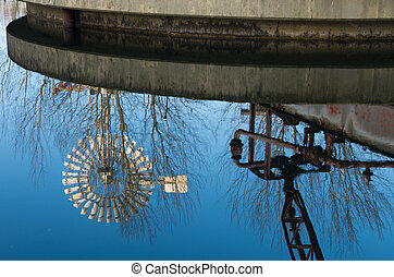 old windmill - Old windmill reflected in a water basin at...