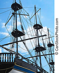 masts and rigging of a old sailing ship over blue sky...