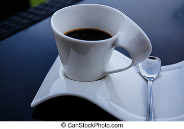 Cup of black coffee on a black table