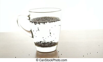 Chia seeds soak up in water glass on white background