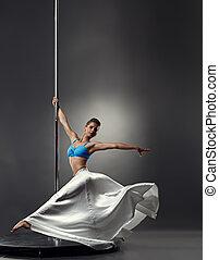 Image of pretty graceful girl dancing on pole