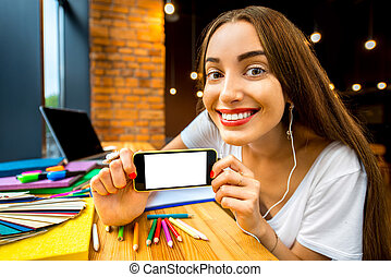 Studing in the cafe - Young woman holding smart phone with...