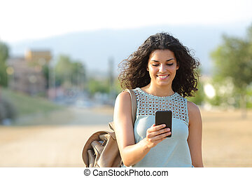 Girl walking and using a smart phone in a town