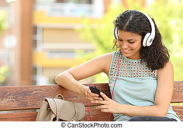 Woman listening to the music in a park - Woman listening to...