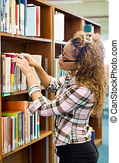 young librarian - a young librarian looking books on the...