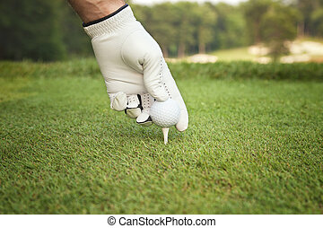 Selective focus of golfers hand placing ball on tee - A...