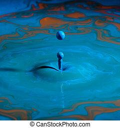 blue paint droplet over color paint surface