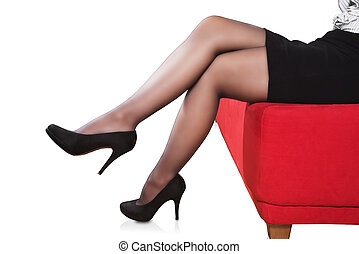 female legs wearing high heels sitting on a red sofa...